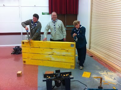 Scouts and Explorers building a raised bed for donation to Edgcumbe